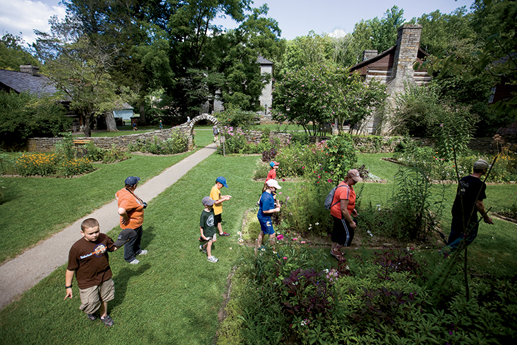 Visitors walk through the heritage gardens at Spring Mill Pioneer Village in Mitchell, Indiana.